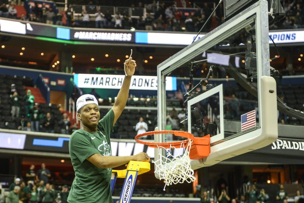 Junior guard Cassius Winston (5) cuts a piece from the net after the game against Duke at Capital One Arena on March 31, 2019. The Spartans defeated the Blue Devils, 68-67. The Spartans are the East Regional Winners and are headed to the Final Four.