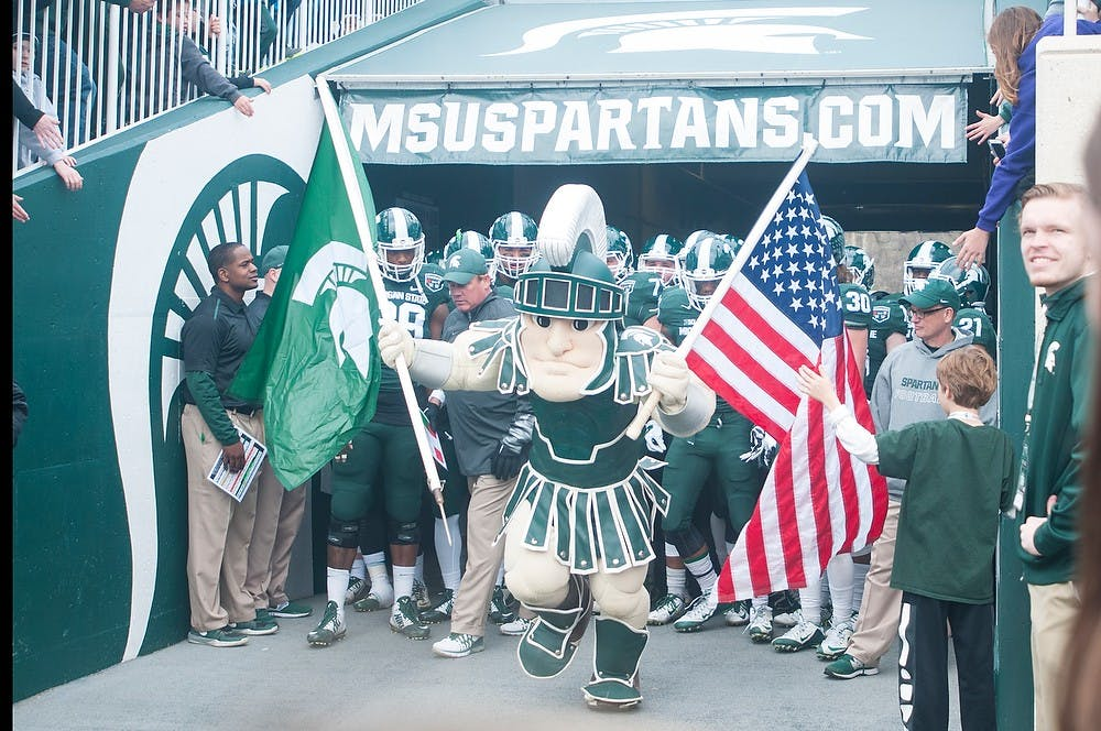 <p>Sparty and the MSU football team run on the field prior to the Green and White Spring Game on April 25, 2015, at Spartan Stadium. The white team defeated the green team, 9-3.</p>