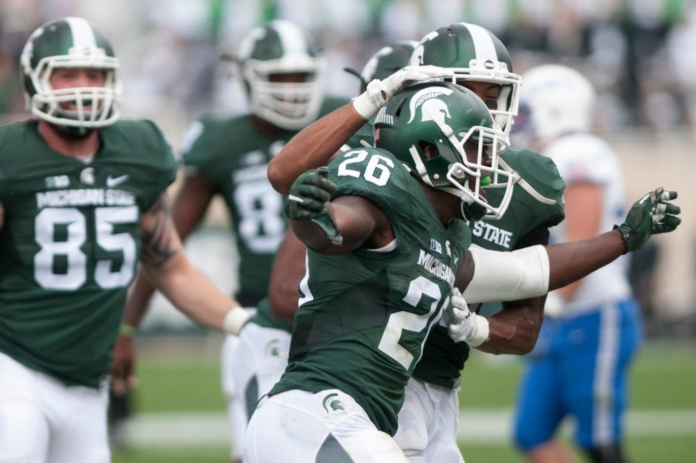 <p>Senior safety RJ Williamson, 26, celebrates his interception with senior cornerback Arjen Colquhoun, behind, in the fourth quarter during the game against Air Force on Sept. 19, 2015 at Spartan Stadium. The Spartans defeated the Falcons, 35-21. Kennedy Thatch/The State News</p>