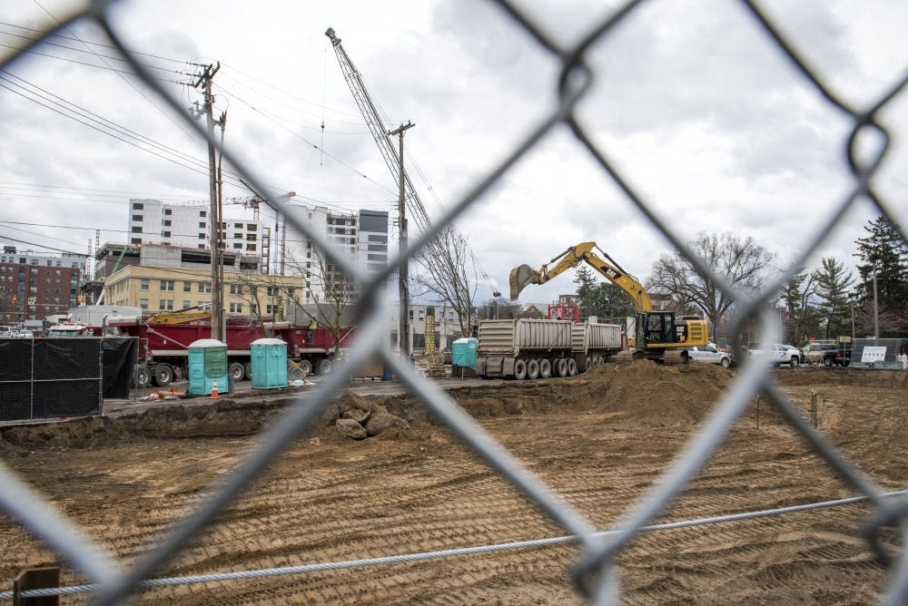 Constructions workers work at the Park District project in East Lansing on April 12, 2019. (Nic Antaya/The State News)
