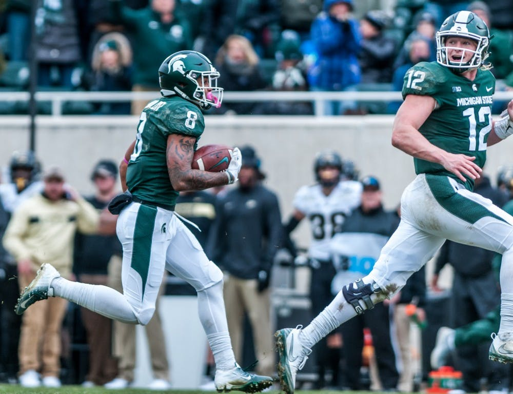 Freshman wide receiver Jalen Nailor (8) runs to the end zone lead by redshirt freshman quarterback Rocky Lombardi (12) during the game against Purdue on Oct. 27, 2018 at Spartan Stadium. The Spartans defeated the Boilermakers 23-13.
