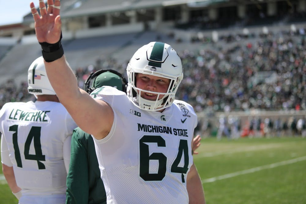 Senior center Matt Allen (64) waves to the crowd before the start of the Green and White game at the Spartan Stadium on April 13, 2019.