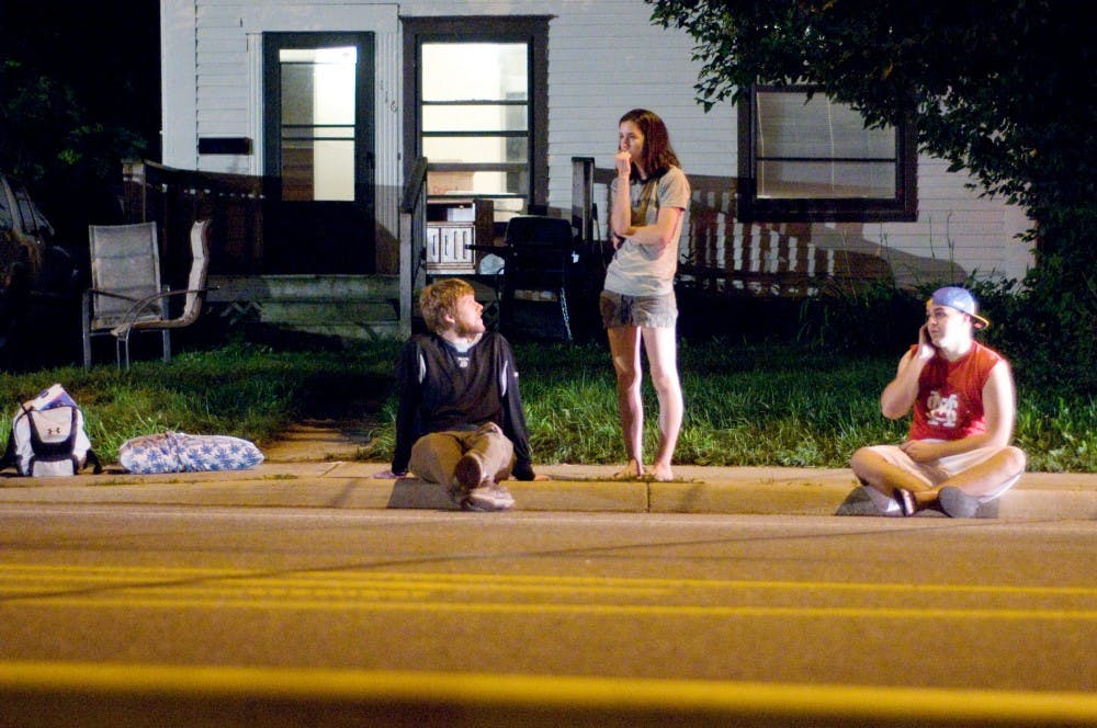 <p>From left, psychology senior Jonathan Bomar, East Lansing resident Sarah Kwiatkowski and journalism senior Steven Miller wait on the curb as East Lansing and Meridian Township firefighters extinguish and investigate a fire that erupted in their apartment building, 129 Burcham Apartments, late Monday night. All residents were evacuated and unharmed.</p>