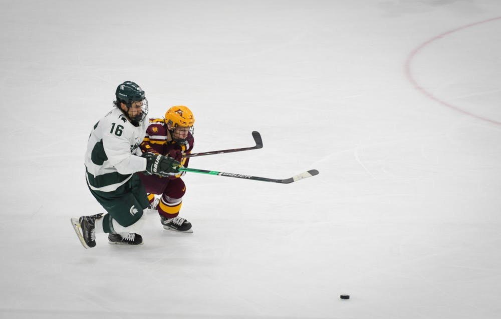 <p>Junior forward Brody Stevens (16) fights for the puck during the hockey game against Minnesota at the Munn Ice Arena on Jan. 10. The Spartans defeated the Golden Gophers 4-1. </p>