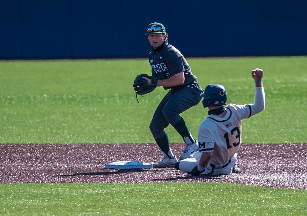 Freshman infielder Trent Farquhar (1) gets Michigan's Griffin Mazur out before throwing it to first, resulting in a double play. The Wolverines made a comeback in the ninth inning to top the Spartans 8-7 at Ray Fisher Stadium on Mar. 21, 2021.