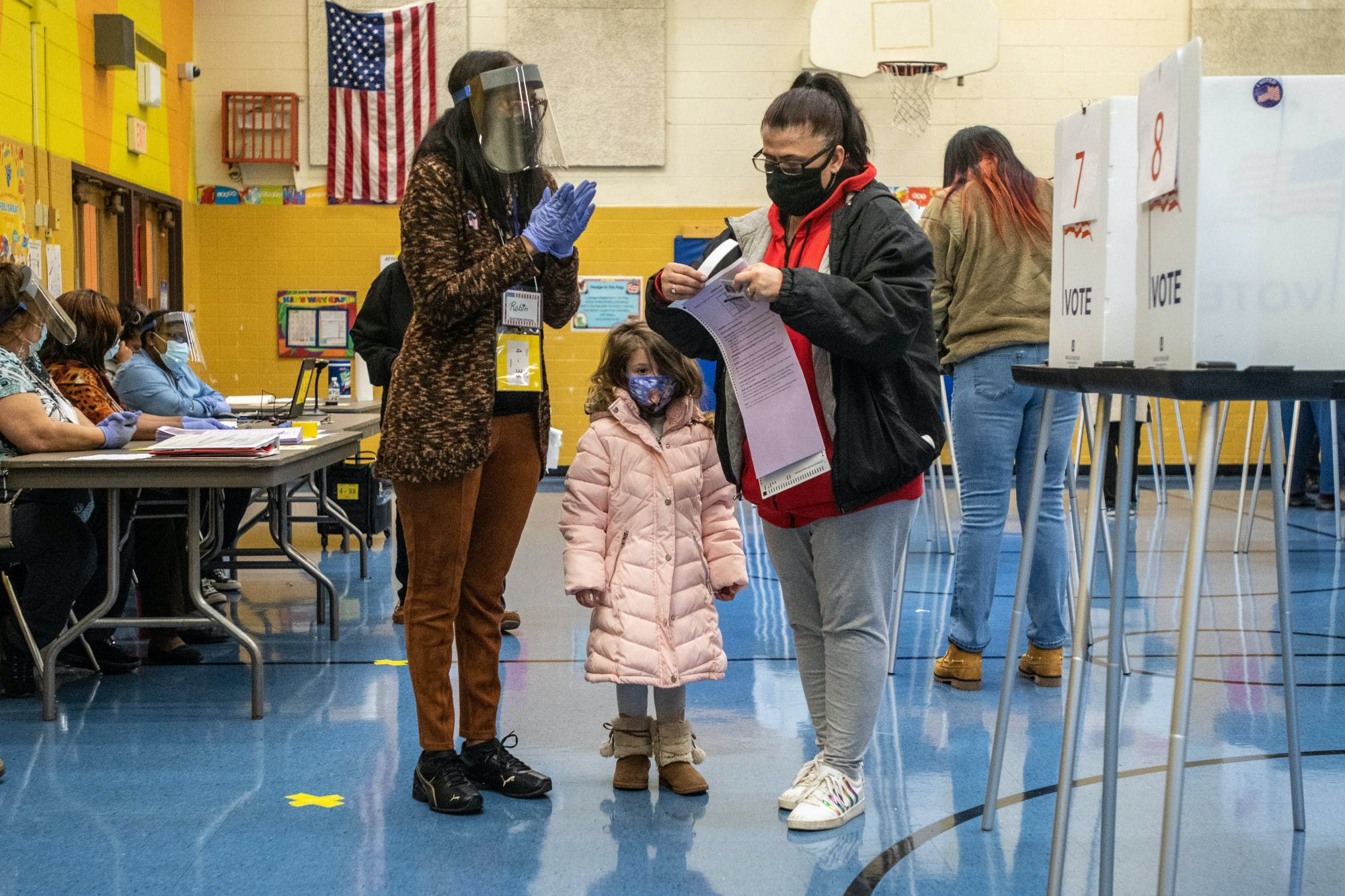Two adults and a child stand in a polling center wearing face masks.