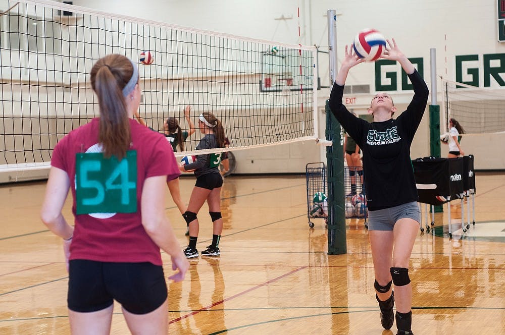 <p>Marketing freshman Jennifer Gerlach, left, warms up with prenursing sophomore Hannah Schroll during club volleyball try-outs on Sept. 23, 2014, at IM Sports-West. Schroll and Gerlach played volleyball together for three years before coming to college. Jessalyn Tamez/The State News</p>