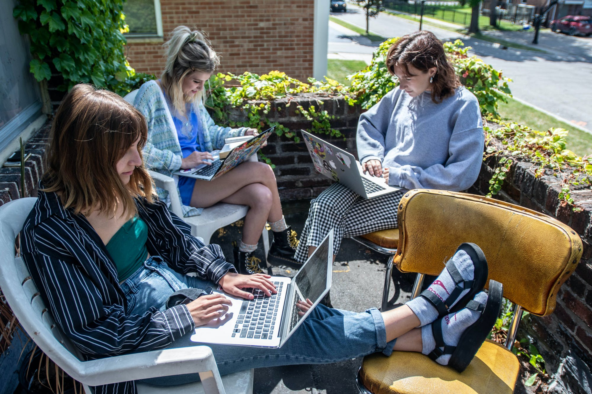 Three people sit in chairs outside on a balcony while working on laptops.