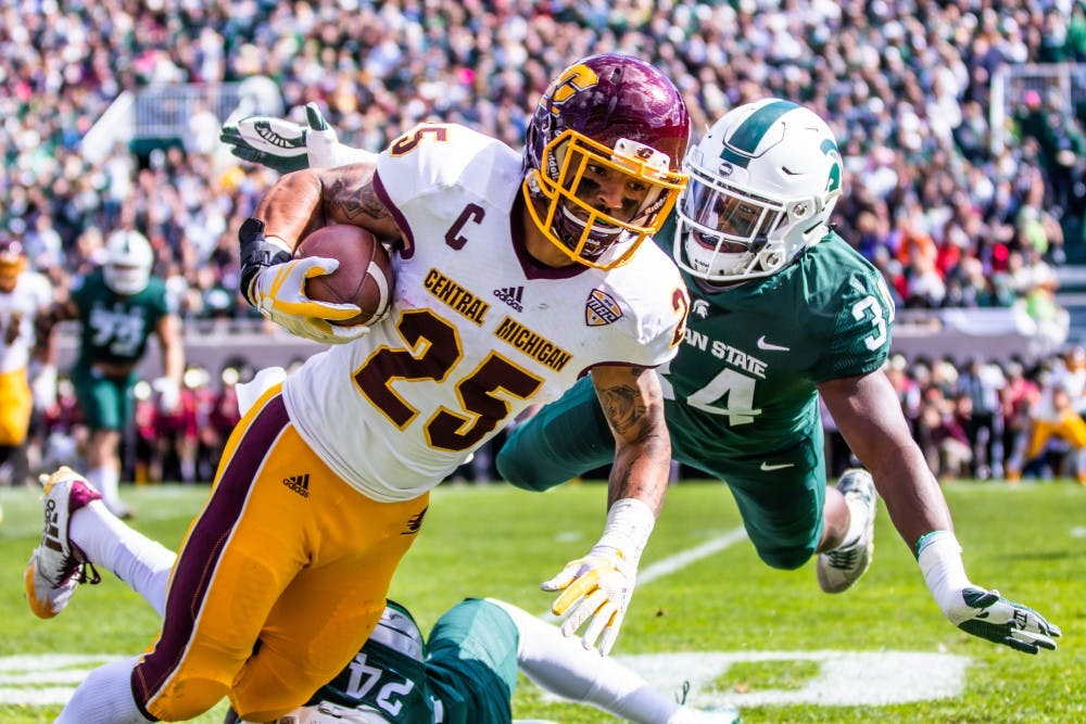 <p>Sophomore linebacker Antjuan Simmons (34) dives to push Central Michigan wide receiver Devon Spalding (25) during the game on Sept. 29, 2018 at Spartan Stadium. The Spartans defeated the Chippewas, 31-20.</p>