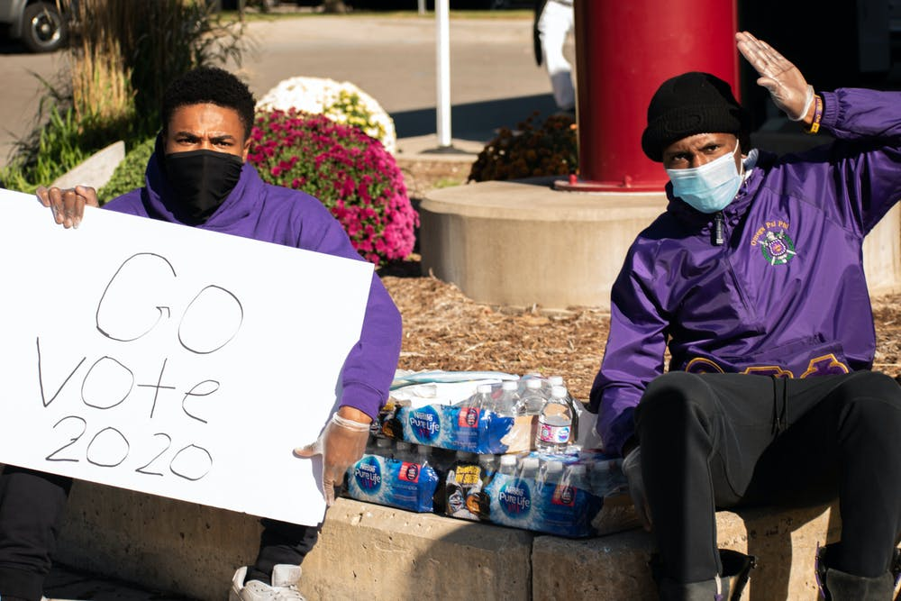 <p>Anthony Hines Jr. (left) and Ryan Thomas (right) of MSU&#x27;s Omega Psi Phi hand out water bottles to voters in front of the East Lansing clerk&#x27;s office during Election Day 2020. In a message directed toward students who hadn&#x27;t voted yet, Hines Jr. firmly said, &quot;Vote, simple.&quot; </p>