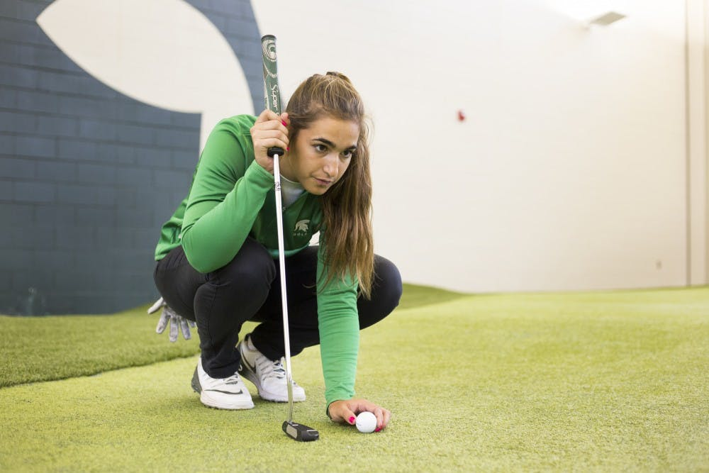 """Business-preference freshman Paz Marfasans practices at the indoor golf course on April 4, 2017 at Lasch Family Golf Center in Lansing.  """"It's pretty different from back home but I love it. The fact that I'm on a team makes me feel like family, without a team would have made my adaptation to America and the school so much more difficult."""" Marfasans said. Marfasans is a student from Barcelona Spain who came to Michigan State in August of 2016 to play golf."""