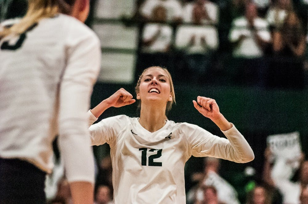 Senior setter Rachel Minarick (12) reacts to a successful play during the game against Michigan on Oct. 18, 2017 at Jenison Fieldhouse. The Spartans secured a 3-1 win against the Wolverines.