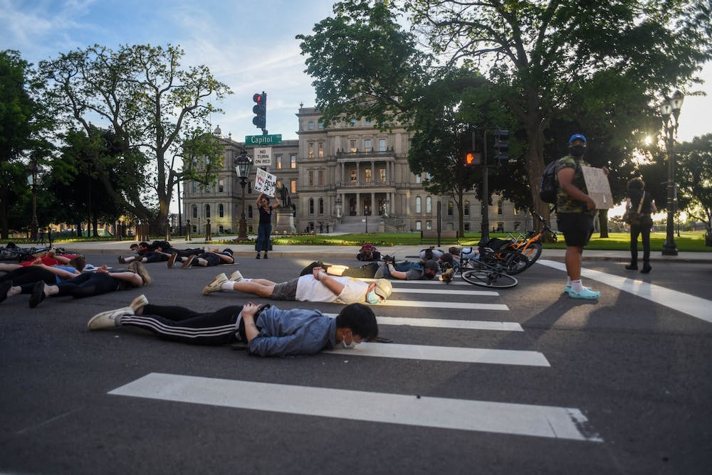 <p>Protesters lay on the ground at a protest around downtown Lansing on June 3, 2020.</p>