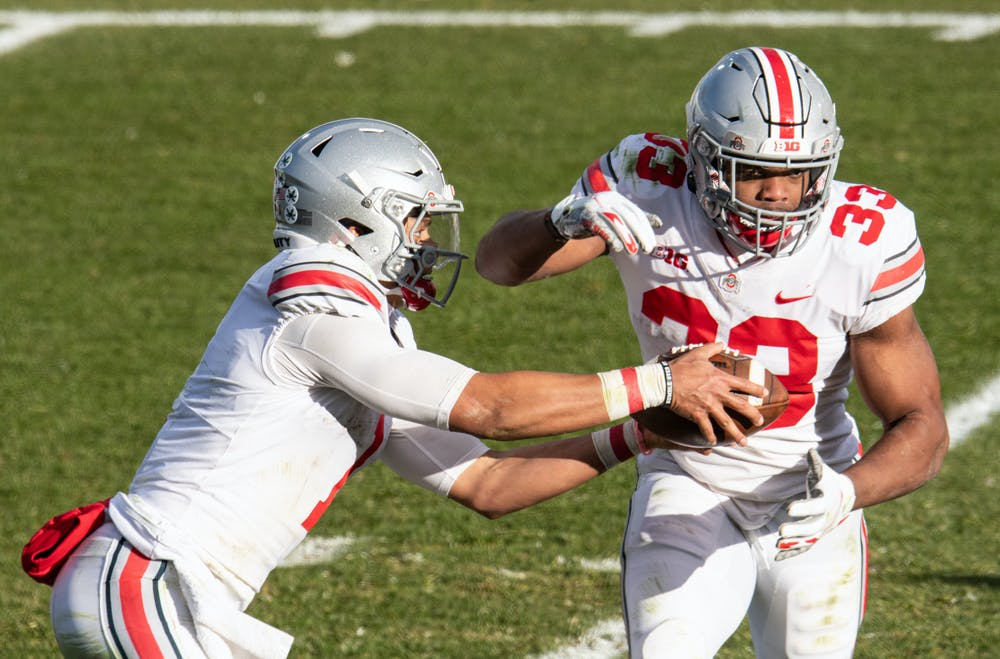 <p>OSU quarterback Justin Fields (1) hands the ball off to Chris Booker (33) in a game against MSU on Dec. 5, 2020.</p>