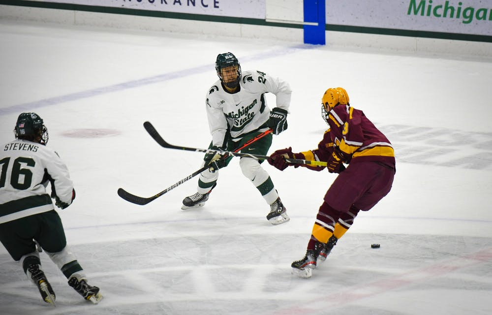 <p>Junior forward Austin Kamer (24) makes a pass during the hockey game against Minnesota at the Munn Ice Arena on Jan. 10. The Spartans defeated the Golden Gophers 4-1. </p>