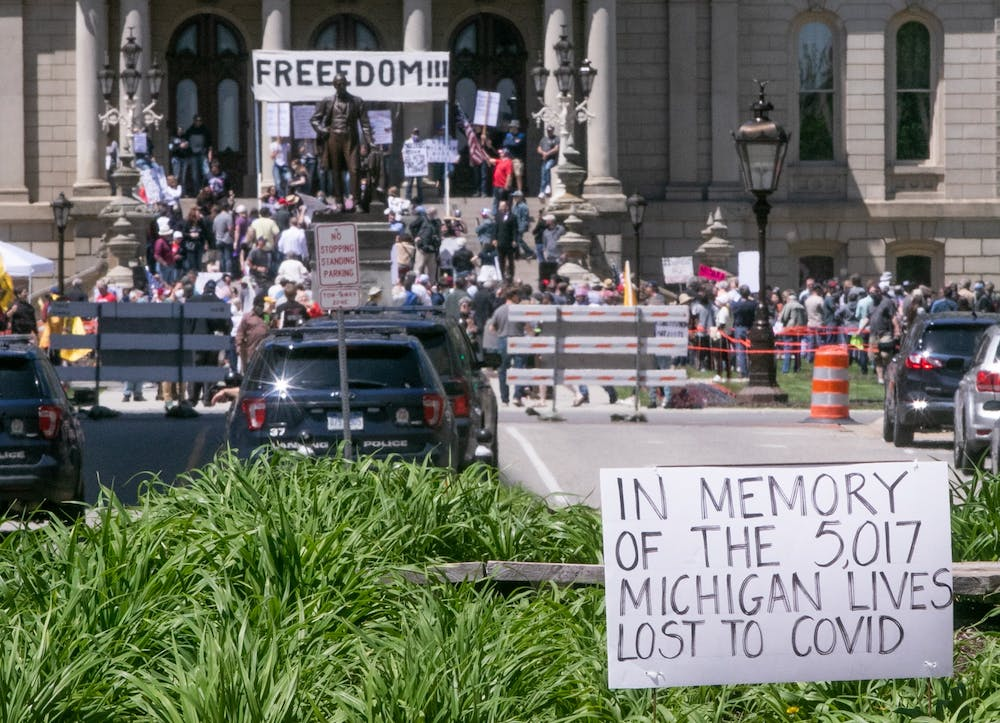 <p>Lines gather in front of the Capitol as people wait to get their haircut at the #OperationHaircut protest in Lansing on May 20, 2020.</p>