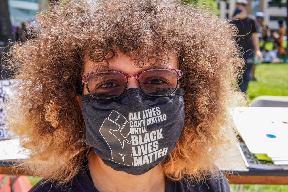<p>A young protester shows her mask during the Black Lives Matter protest at the Michigan State Capitol on June 29, 2020.</p>