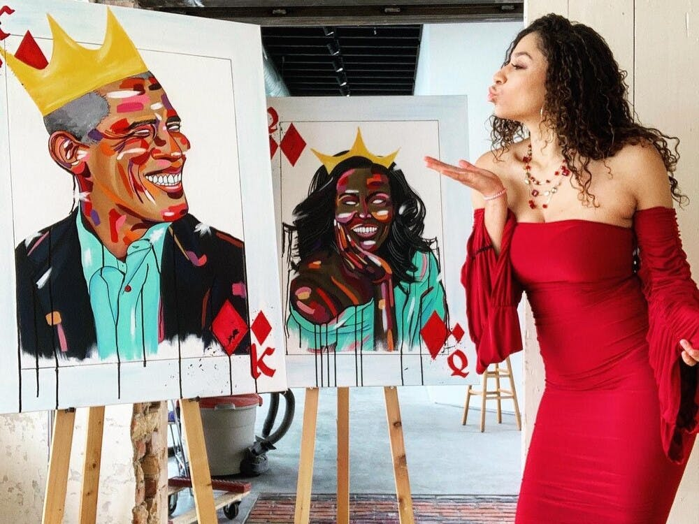 Lansing-based artist Mila Lynn poses with her portraits of Barack and Michelle Obama, which are part of her 'Black is King' project. Photo courtesy of Mila Lynn.