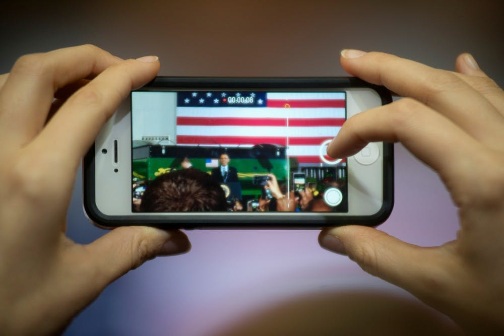 <p>An attendee records President Barack Obama's speech about the farm bill on her phone Feb. 7, 2014, at the Mary Anne McPhail Equine Performance Center. After the speech, Obama signed the bill into law. Julia Nagy/The State News</p>