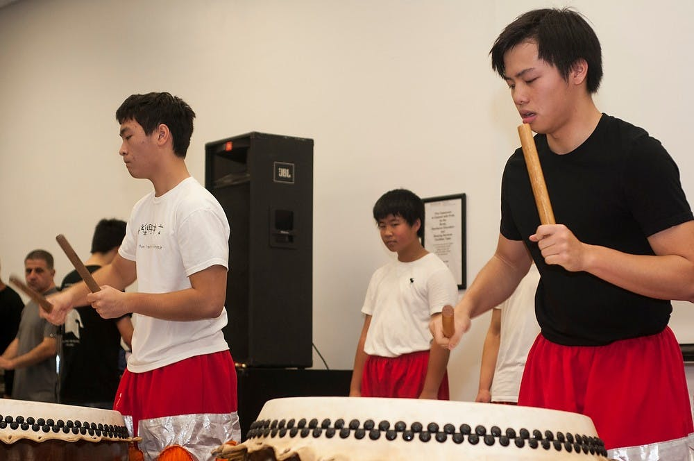 <p>Northville, Mich., residents Andy Tang, left, and Nathan Low, right, play Chinese drums for the lion dance Nov. 17, 2013, at Brody Hall Complex. The Global Festival gave the Lansing community a chance to explore cultures from all around the world.</p>