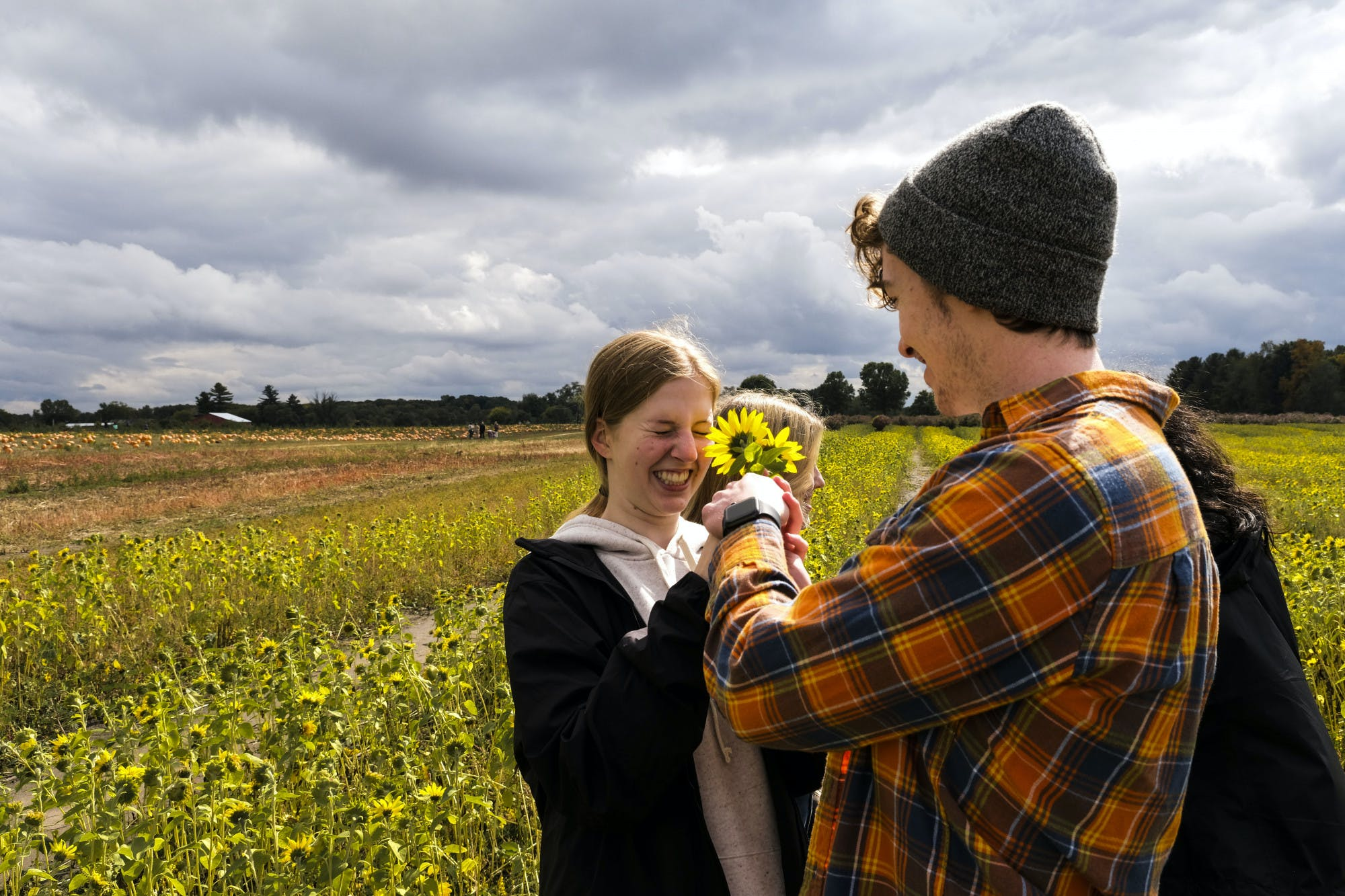 Two people stand in a field and hold sunflowers.