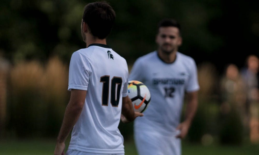 Sophomore midfielder Giuseppe Barone (10) hands off the ball to junior defender John Freitag (12) during a game against Dartmouth on Sep. 1, 2017 at DeMartin Stadium at Old College Field. The Spartans defeated the Big Greens 1-0.