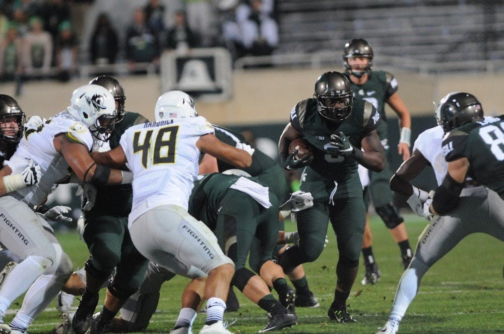 <p>Then-freshman running back LJ Scott runs the ball during the second quarter of the game against Oregon on Sept. 12, 2015 at Spartan Stadium. The Spartans defeated the Ducks 31-28. Joshua Abraham/The State News</p>