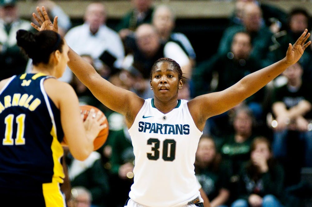 Redshirt senior forward Lykendra Johnson throws up her arms while defending Michigan forward Sam Arnold Wednesday night at Breslin Center. Johnson snagged five rebounds for the Spartans during the 60-55 victory over the Wolverines. Matt Hallowell/The State News