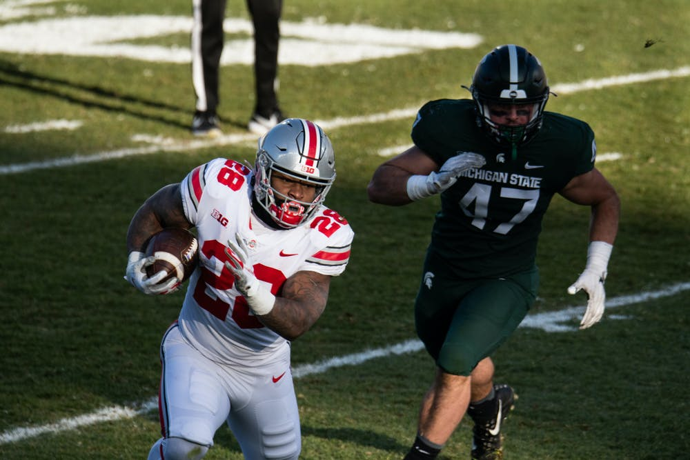 OSU running back Miyan WIlliams (28) carries the ball, chased by MSu defensive end Jeff Pietrowski (47).