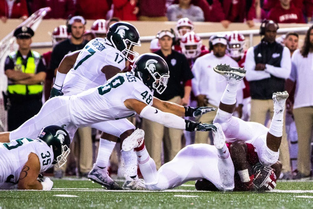 <p>An Indiana ball carrier is tackled by a group of Spartans during the game against Indiana on Sept. 22, 2018 at Memorial Stadium. The Spartans defeated the Hoosiers, 35-21.</p>