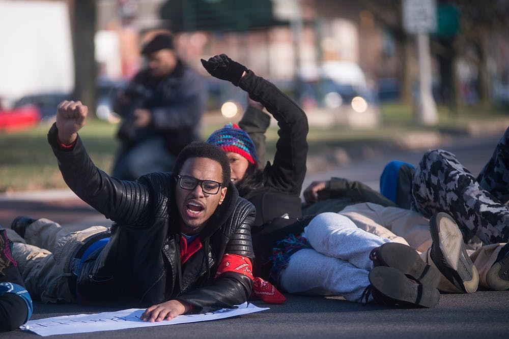 <p>Supply chain management sophomore Steve Cleaves-Jones chants and lays down in the middle of Grand River Ave. in protest Dec. 6, 2014, during a protest which went down Grand River Ave., to the MSU Union and ended to the Beaumont Tower. The group of students shut down Grand River Ave., in East Lansing by marching and laying down in the middle of the street in protest of police violence against black people. Erin Hampton/The State News</p>
