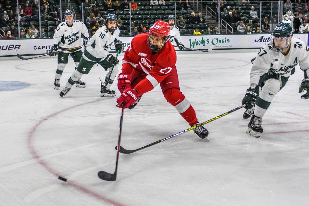 <p>Redshirt senior left defense Jerad Rosburg (57) fights for the puck against Cornell center Morgan Barron (27) during the game against Cornell at Munn Ice Arena on Nov. 1, 2019. The Spartans fell to the Big Red, 3-2.</p>