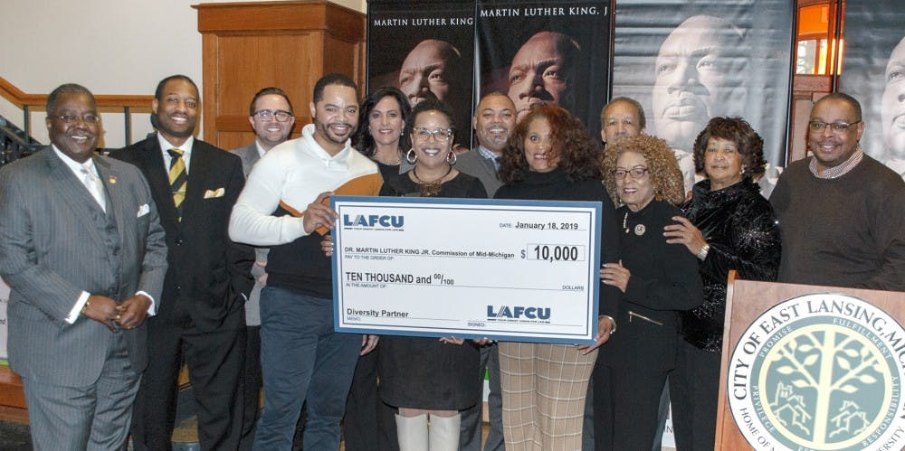 <p>Kelli Ellsworth Etchison representing LAFCU, center, presents a ceremonial check to the Dr. Martin Luther King Jr. Commission of Mid-Michigan | Photo courtesy of Jan Jenkins, director of public relations for Edge Publicom&nbsp;</p>