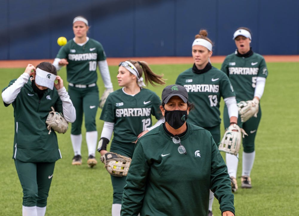 Coach Jacquie Joseph walks towards the dugout with her team behind her after a timeout. The Wolverines crushed the Spartans in a 6-1 win back on their home turf on April 14, 2021.