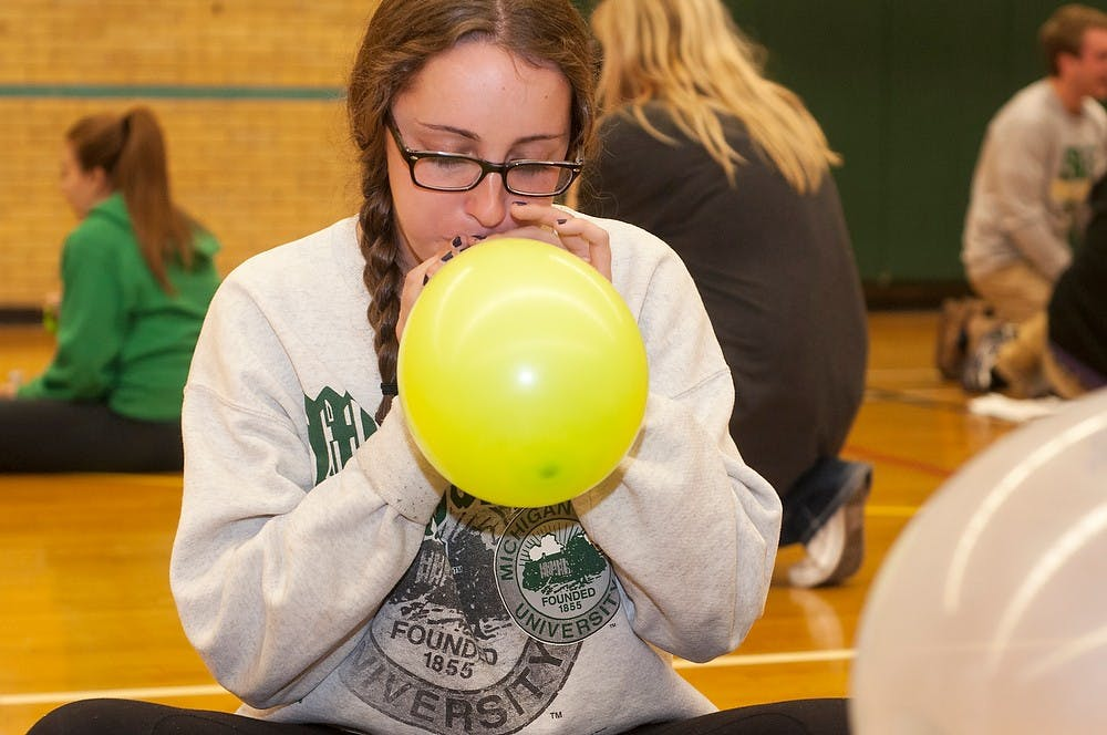 <p>Pre-medical freshman Jaqui Somes blows up a balloon for the balloon tower Nov. 15, 2013, at IM Sports Circle. Students stayed up all night playing games, watching videos and eating to celebrate their fundraising for St. Judes research hospital.</p>