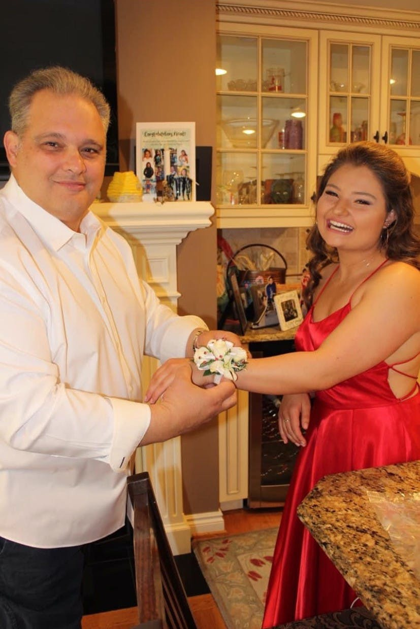 A middle-aged man in a white dress shirt puts a wrist corsage on a young girl in a red dress.