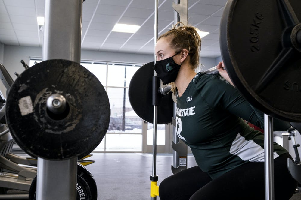 Junior MSU Volleyball player Elena Shkylar doing a weighted squat on February 18, 2021. Elena says the part of her body she likes most about herself are her legs.