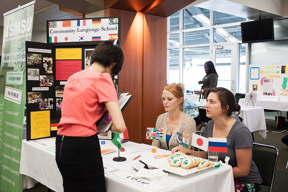 <p>Senior special education major Christine Chern (left) stops by the Community Language School booth to speak with Heather Brown (middle) and Hannah Jenuwine (right) at the Earn Learn & Intern Fair held on the fourth floor of Spartan Stadium on Wednesday, Sept. 8. Griffin Zotter/The State News</p>