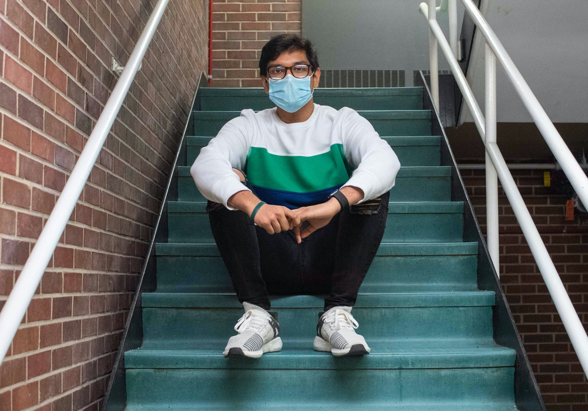 A person wearing a face mask, sweatshirt, jeans, sneakers and glasses sits on the stairs of a building stairwell, posing for a photo.
