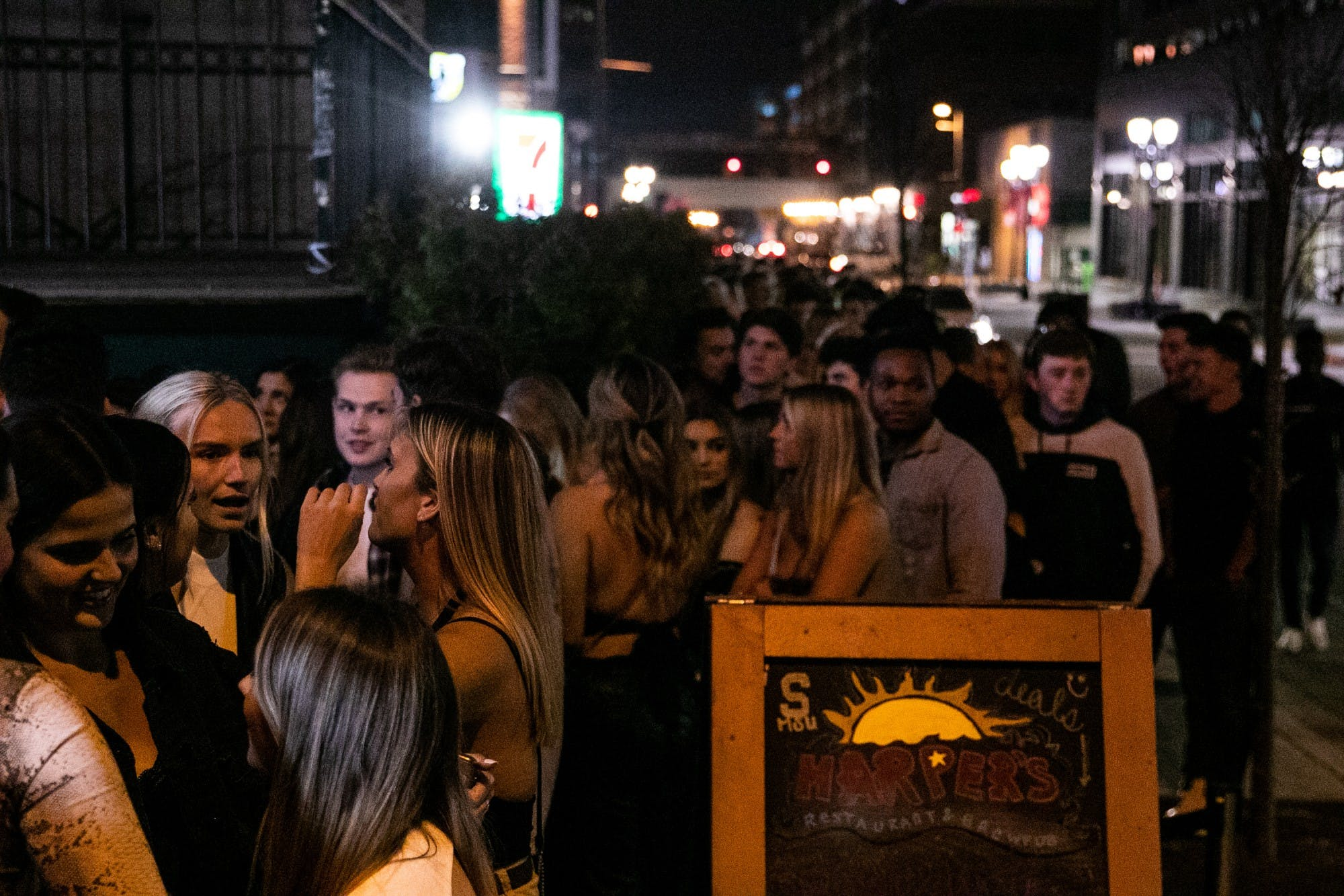 Young adults talk with each other in groups as they wait in a line. Next to the line is a sign that reads 'Harper's Restaurant and Brewpub.' Behind the line are city lights at night.'