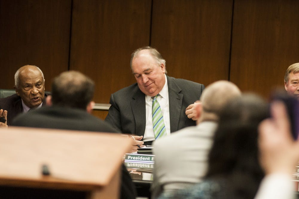 <p>Interim President John Engler looks down during the Board of Trustees meeting on April 13, 2018 at Hannah Administration Building. (C.J. Weiss | The State News)</p>