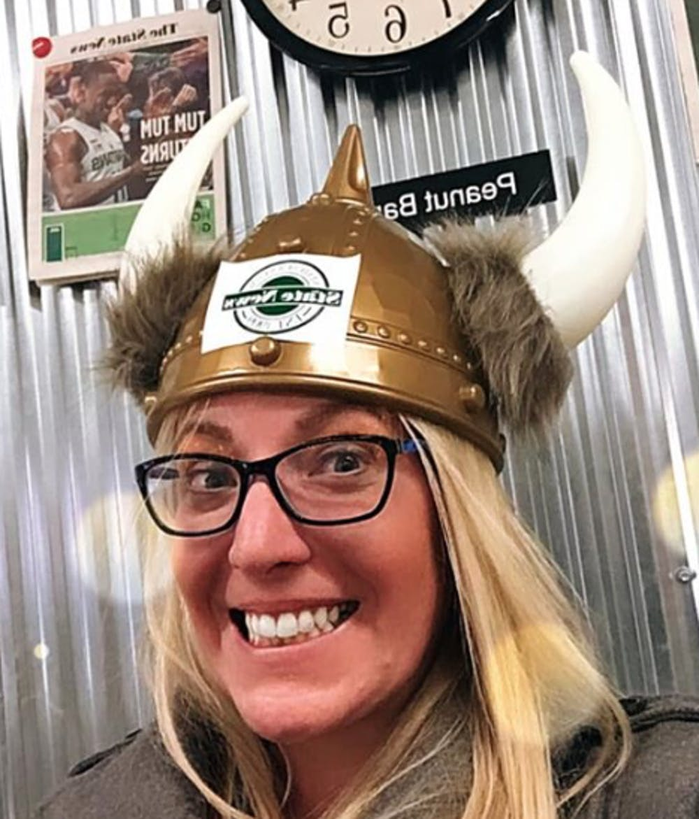 <p>Dawn Klemish (&#x27;05), a writer and producer with MLB.com, gets reacquainted with The State News Viking Helmet (awarded to the newsroom staffer of the week) during her visit to State News offices in January of 2020.</p>
