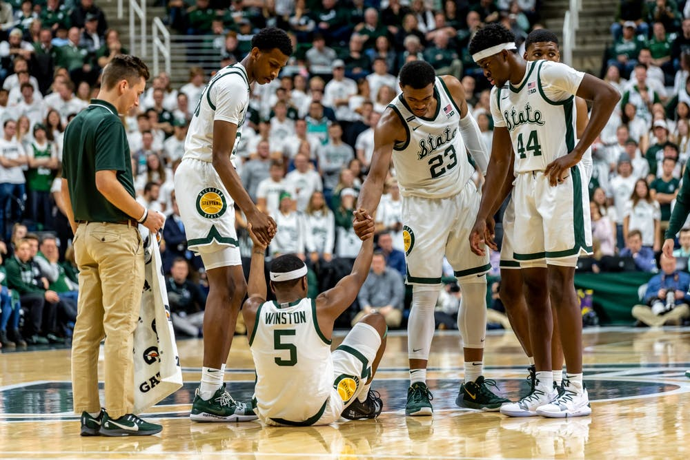 Senior guard Cassius Winston (5) is helped up by his teammates during a game against Northwestern.The Spartans defeated the Wildcats, 79-50, at the Breslin Student Events Center on January 29, 2020.