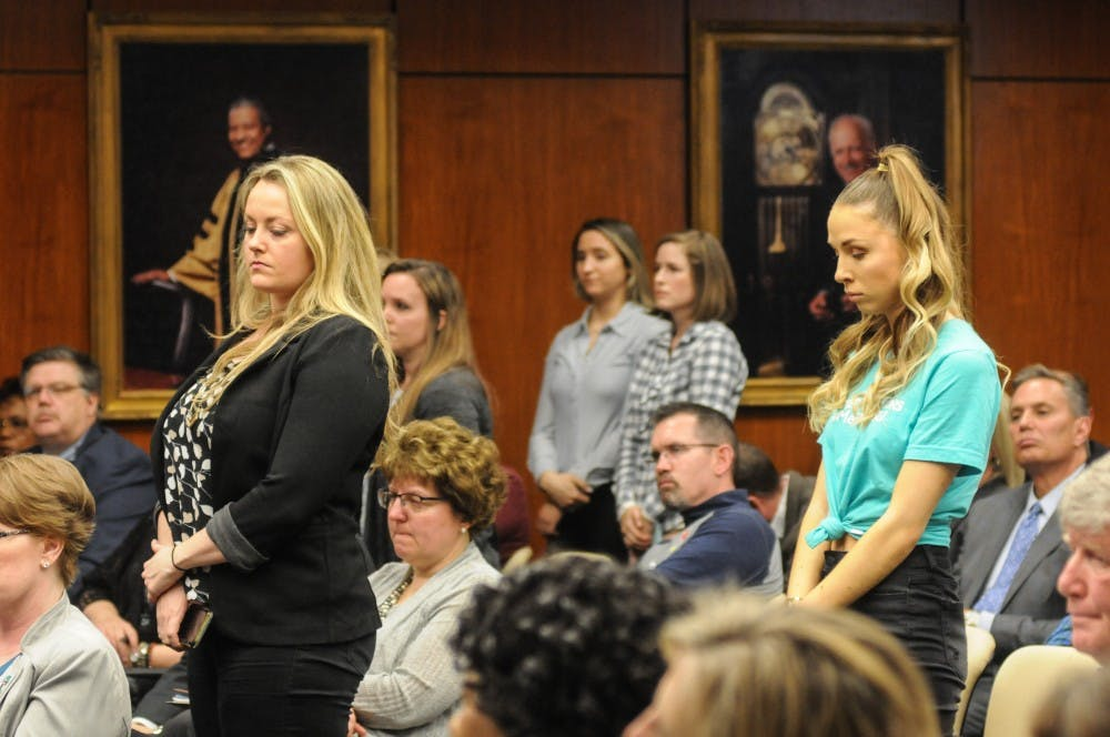 <p>Survivors stand in the audience at the Board of Trustees meeting on April 12, 2019 at the Administration Building.</p>