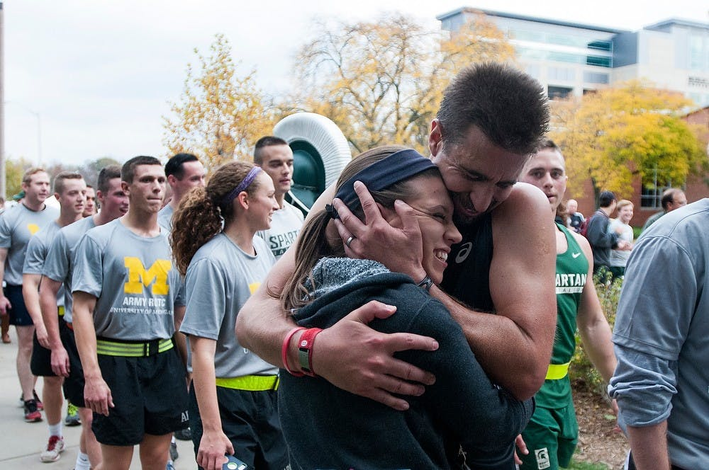 <p>Playmakers ultra-marathoner Michael Richmond clutches his daughter after the 11-hour, 64 mile run from Ann Arbor to East Lansing for Alex's Great State Race on Oct. 24, 2014, at Dem Hall. Dylan Vowell/The State News</p>
