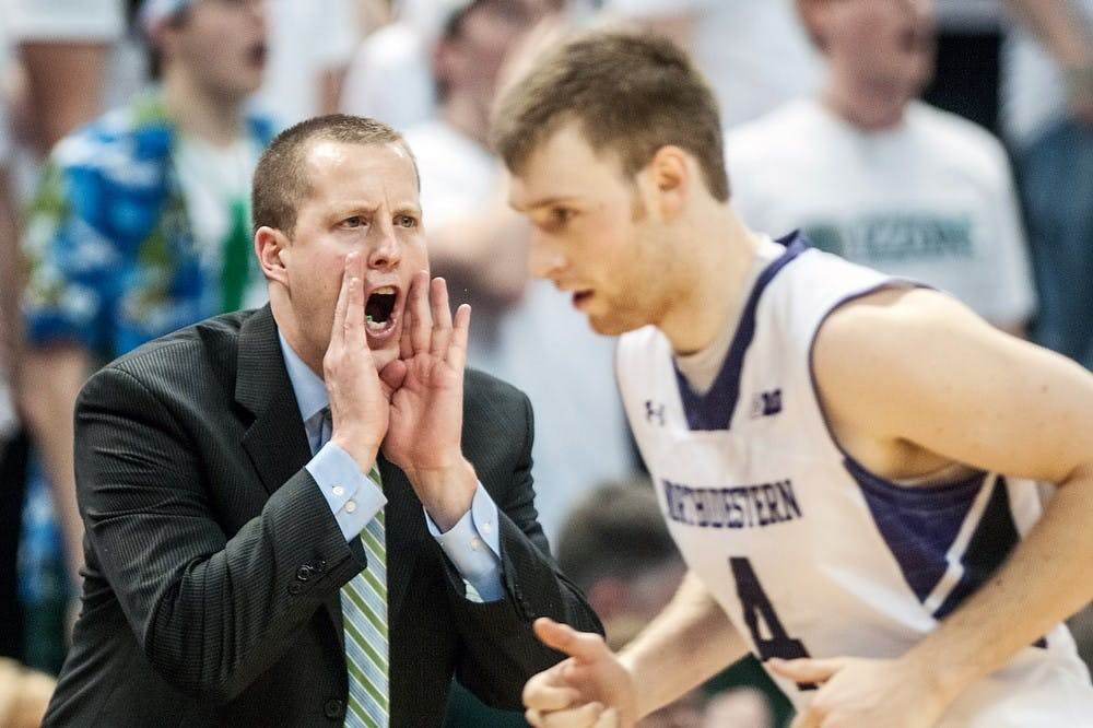 MSU assistant coach Dane Fife yells from the bench in the early second half of the game as Northwestern guard Alex Marcotullio rushes past him. The Spartans defeated the Wildcats, 71-61, on March 10, 2013, at Breslin Center. Justin Wan/The State News