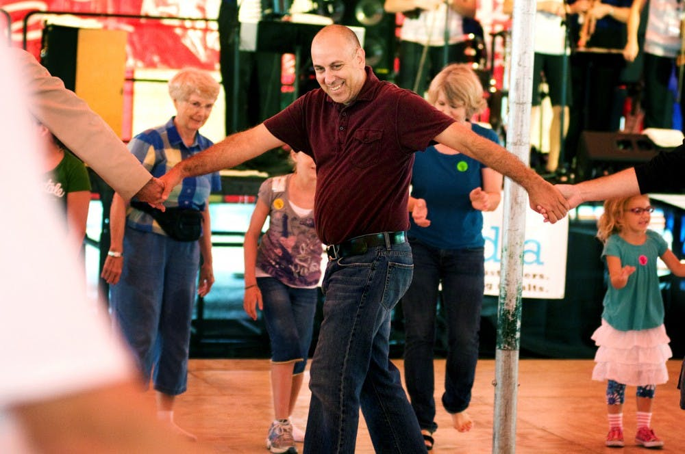 <p>East Lansing resident John Kodeski holds hands and spins in a circle with other men participating in a group polka Sunday at the Great Lakes Folk Festival in East Lansing.  </p>