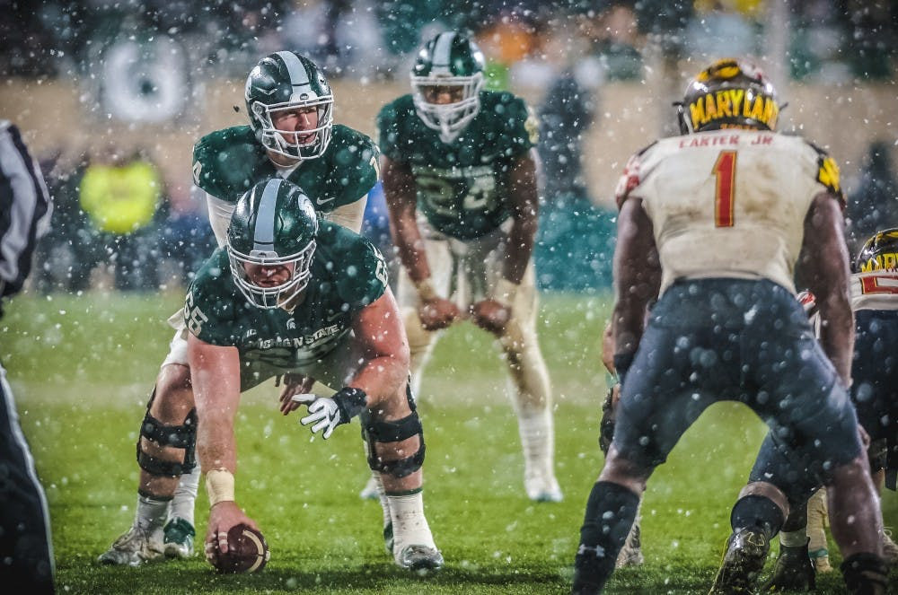Senior offensive lineman Brian Allen (65) prepares to snap the ball to sophomore quarterback Brian Lewerke (14) during the game against Maryland on Nov. 18, 2017, at Spartan Stadium. The Spartans defeated the Terrapins, 17-7.
