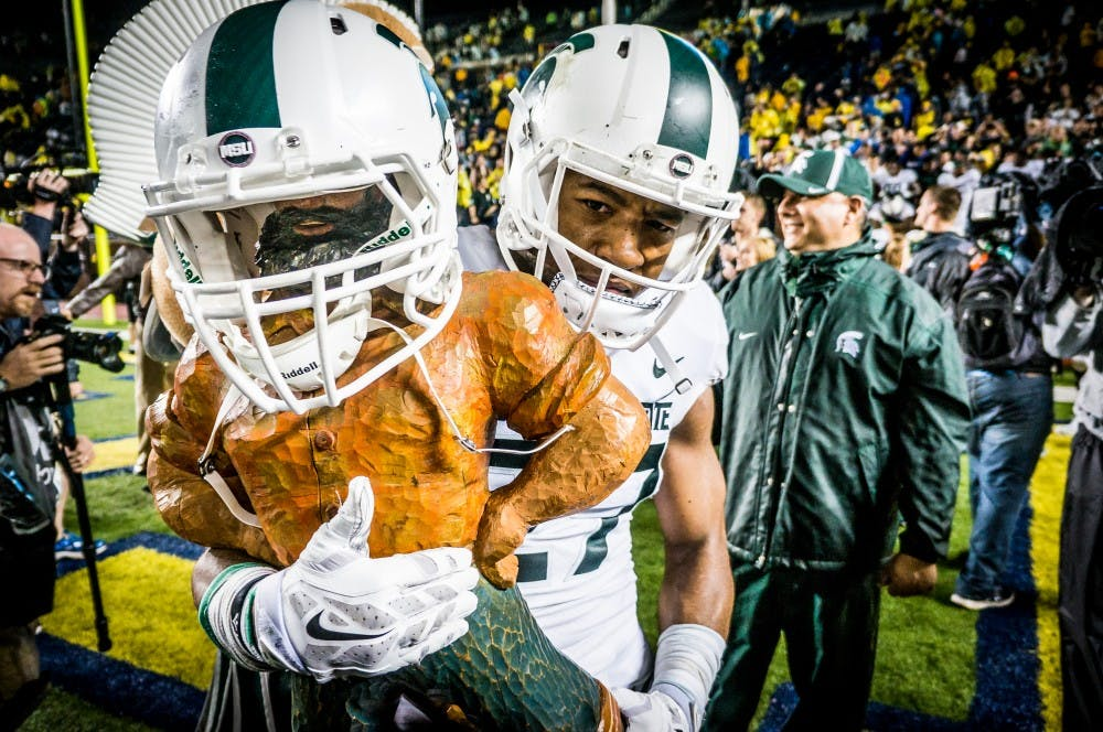 <p>Junior safety Khari Willis (27) holds the Paul Bunyan Trophy &nbsp;after the game against Michigan on Oct. 7, 2017 at Michigan Stadium. The Spartans defeated the Wolverines, 14-10.</p>