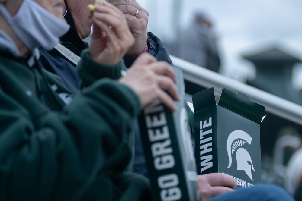 Michigan State fans eating popcorn during Michigan State's game against Purdue on April 12, 2021 at McLane Stadium at Kob's Field in East Lansing.